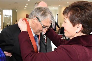 Image of Dame Patsy placing the insignia of a CNZM around Jim Anderton's neck