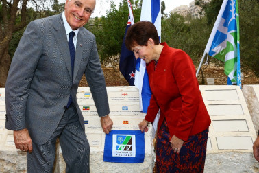 an image of Dame Patsy and Sir David unveil a plaque to mark the planting of an olive tree at the Grove of Nations