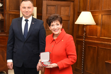 Image of Dame Patsy with a medallion presented to her by HE Andrzej Duda