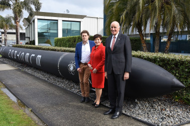 Image of dame Patsy, Sir David and Peter Beck with a rocket outside Rocket Lab