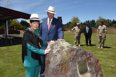 an image of Dame Patsy and Sir David touching a stone of remembrance on the marae