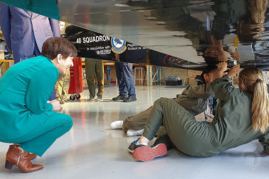 Image of Dame Patsy watching some students fix a plane's undercarriage
