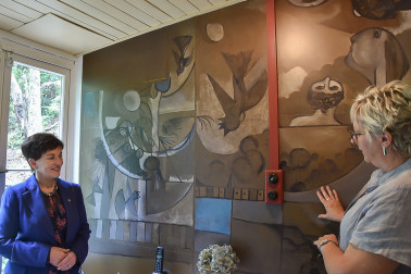 image of McCahon House Trust Chair Cynthia Smith taking Dame Patsy through the history of the mural in the kitchen