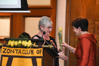 Image of Dame Patsy receiving a Zonta yellow rose from Souella Cumming