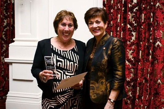 An image of Dame Patsy presenting an Award for Outstanding Service to Mrs Carol Calkoen