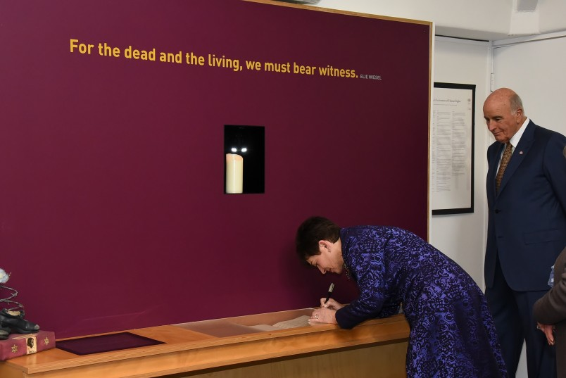 An image of Dame Patsy inscribing a memorial stone