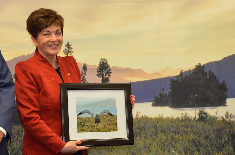 an image of Dame Patsy holding a photograph of an endangered Antipodean albatross