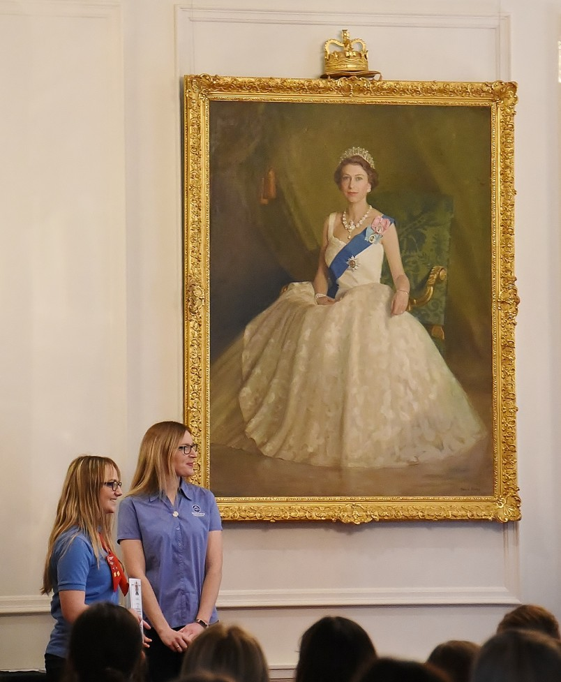 Image of the Queen's Guide award presentation in front of the portrait of the Queen