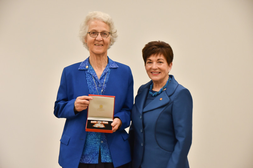Image of Sr Margaret Anne accepting Sr Catherine's QSM for the Sisters of Compassion archives