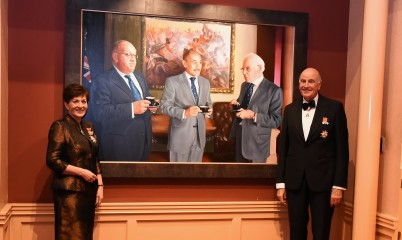 image of Dame Patsy and Sir David with a portrait of previous Governors-General