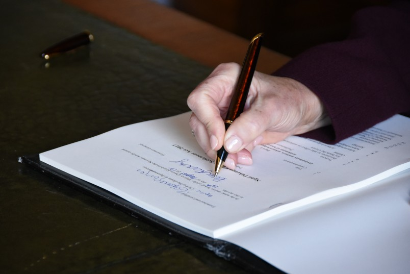 Image of Dame Patsy's hand as she signs the Ngāti Pūkenga Claims Settlement Bill