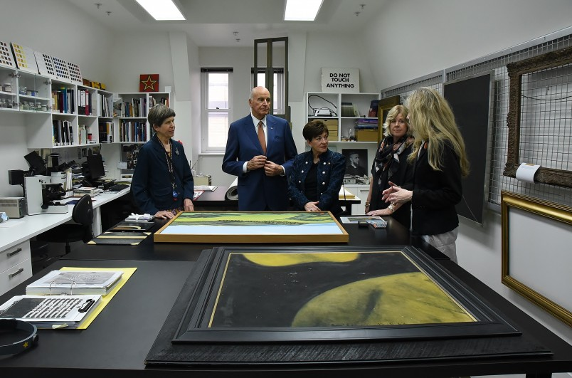 Image of Dame Patsy and Sir David with works by Colin McCahon and Don Binney waiting for attention in the Auckland Art Gallery workshop