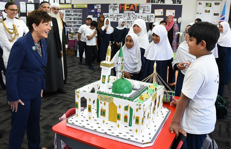 Image of Dame Patsy checking out a model of a mosque built by students