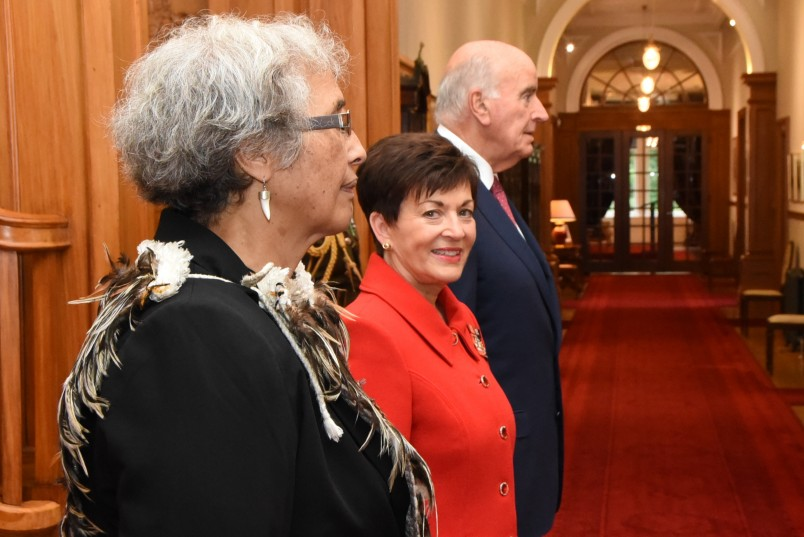 Image of Dame Patsy and Sir David with kuia Te Ripowhai Higgins waiting for the arrival of the King and Queen of Tonga