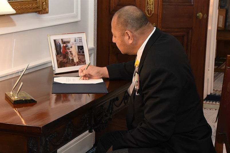 Image of The King of Tonga, King Tupou VI signing the Visitor Book