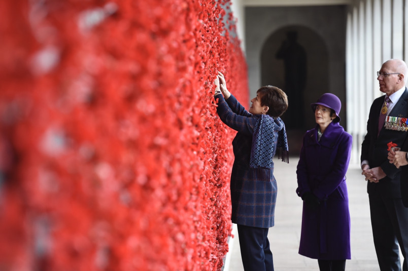 Image of Dame Patsy adding a poppy beside a name on the Roll of Honour