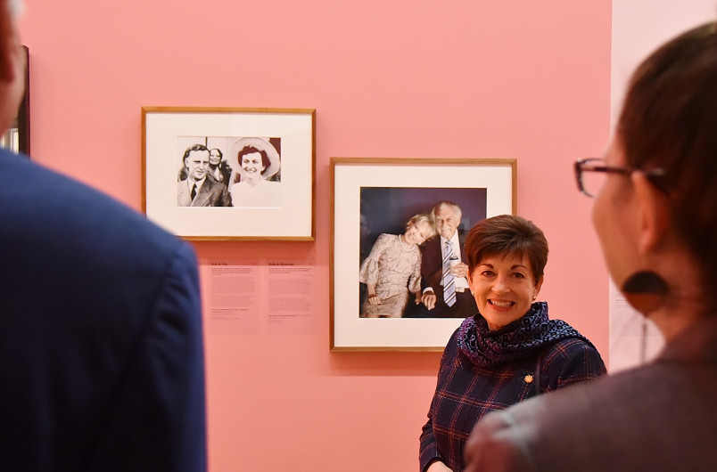 Image of dame Patsy with a photo of Joh Bjelke-Petersen in the background