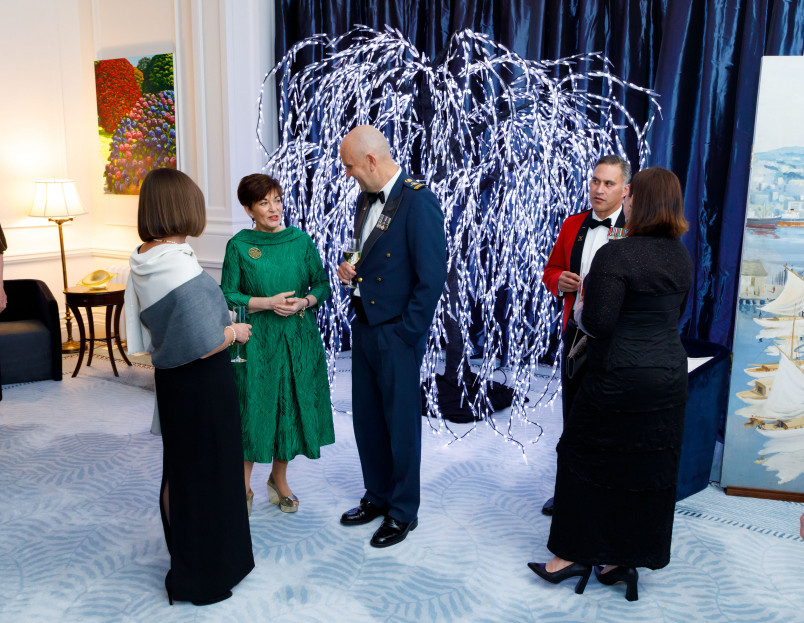 Dame Patsy Reddy with guests by a light up tree