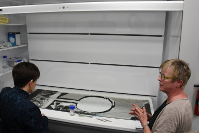 Image of  Dame Patsy and Objects Conservator, Annette McKone discussing the work being done on a Colin McCahon painted glass window