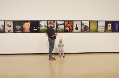 Image of a young boy and his dad looking at art