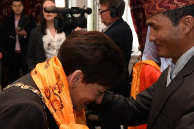 Image of Dame Patsy being presented with Nepalese scarves