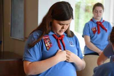Image of a Girl Guide checking her tie