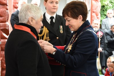 Image of Dame Patsy pinning on Dame Tariana's insignia