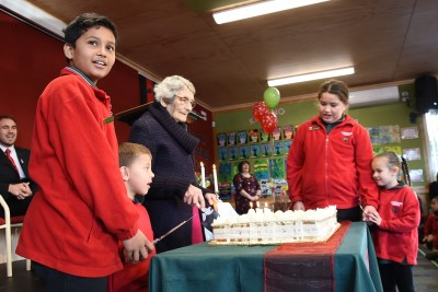 an image of Centenarian Mrs June Hall, an ex pupil, helps cut the school's birthday cake