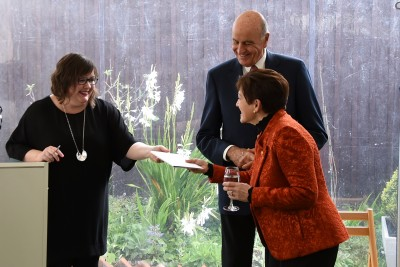 Image of Dame Patsy being presented with a copy of Te Whare Tāre, the first Te Reo translation of The Dolls House -