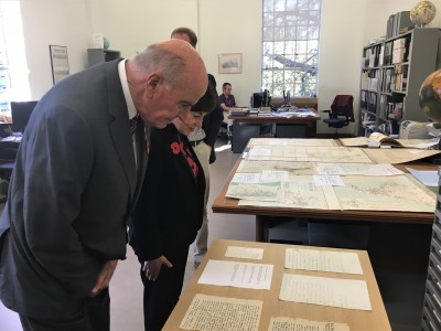 an image of Dame Patsy and Sir David inspecting early letters and maps of New Zealand