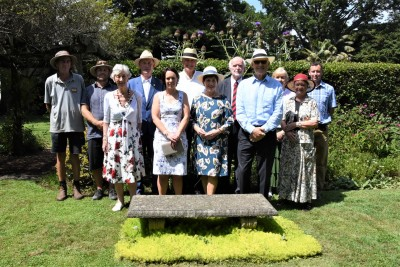 an image of Grounds Committee members and their guests joined Dame Patsy, Sir David and Government House gardeners in front of a bench dedicated to Sir Frank and Lady Mappin