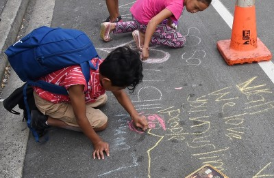 Image of children drawing messages of support on the footpath outside the mosque