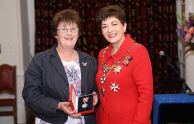 Image of Mary Butler accepting a QSM on behalf of The late Mr Rod Eatwell