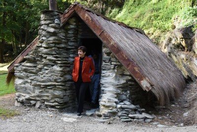 Image of Dame Patsy exiting a miner's hut