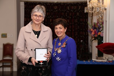 Image of  Josie Snook accepting the insignia on behalf of the late Professor Emeritus Ivan Snook, MNZM, for services to education
