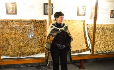Dame Patsy with some of Okains Bay Museum's beautiful korowai