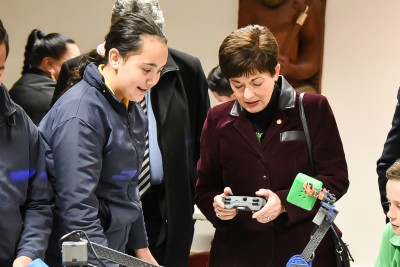 Image of a student helping Dame Patsy