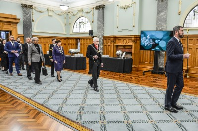 Image of Black Rod leads Dame Patsy and other dignitaries through the Grand Hall to the Legislative Council Chamber