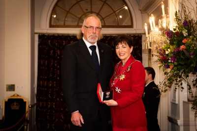Image of Stuart Cameron accepting the QSM on behalf of his father Fraser