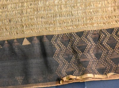 Detail of a large, very finely woven cloak, featuring dog-skin trim