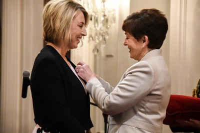 Image of Dame Patsy pinning on Felicity's insignia