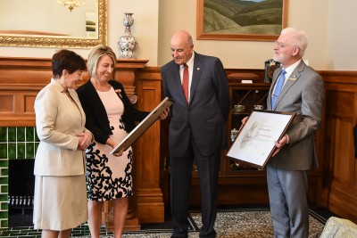 Image of Felicity gapes being presented with her certificate and a framed portrait of Florence Nightingale
