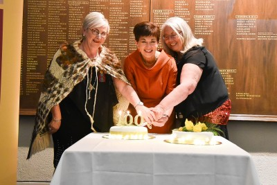 Image of Dame Patsy helping to cut the cake