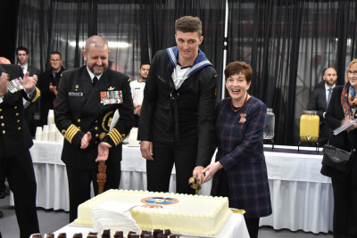 Image of Dame Patsy cutting the cake with the youngest sailor Able Marine Technician Samuel Marsh