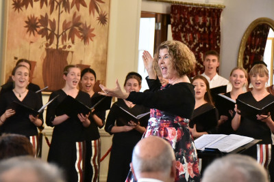 """Image of NZSSC Music Director Sue Densem bringing in the audience for """"Jingle Bells"""""""