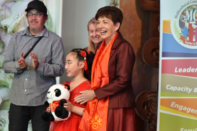 Dame Patsy Reddy presents a panda bear as a prize