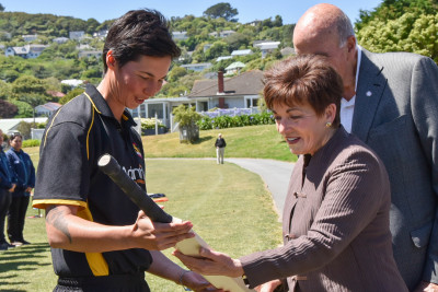 Dame Patsy Reddy being presented with a cricket bat