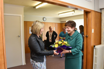 Robyn Morris presenting Dame Patsy with flowers