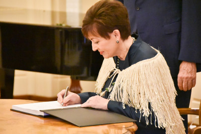 Image of Dame Patsy signing the Visitor Book